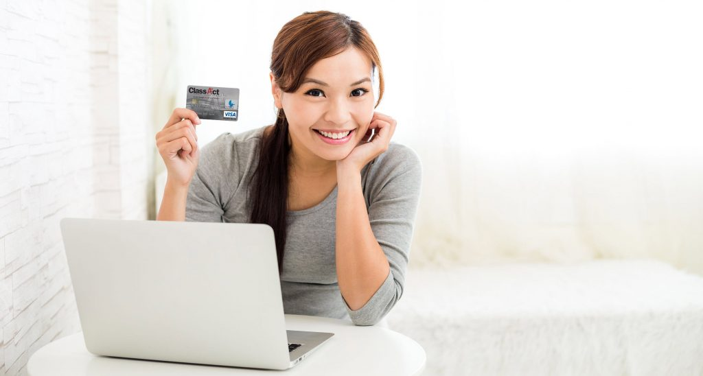 Woman holding a credit card next to a laptop computer