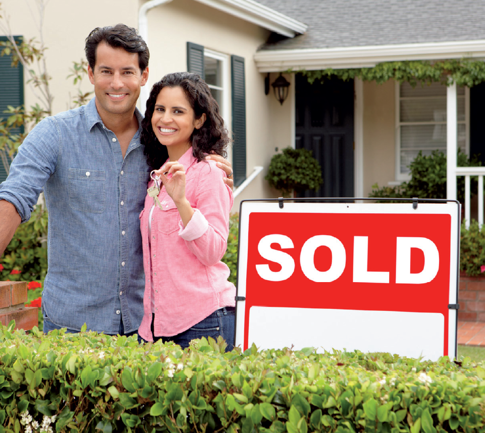 "A man and woman in front of a house with a ""sold"" sign"