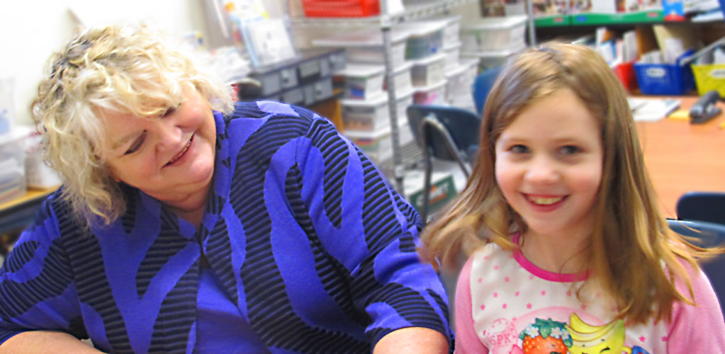 Smiling blonde woman sitting beside a smiling young girl