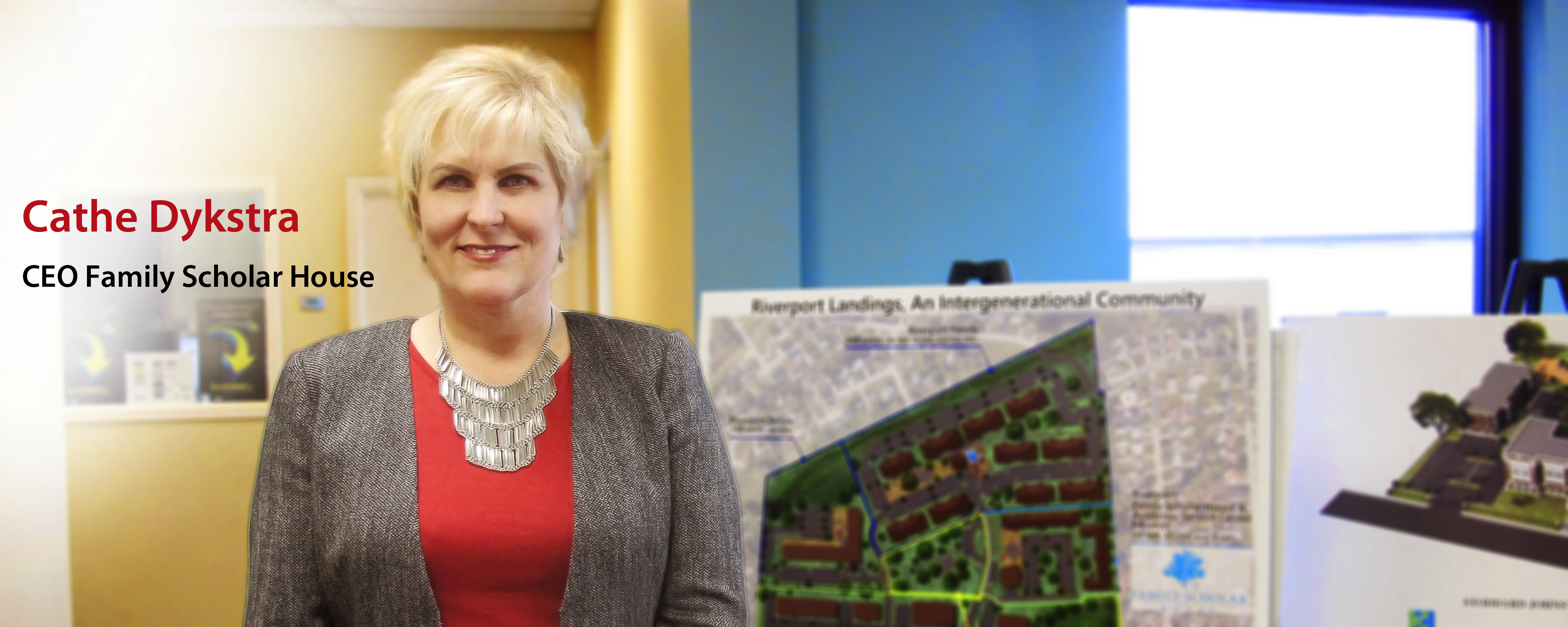 Cathe Dykstra - CEO of Family Scholar House - standing in front of building plans