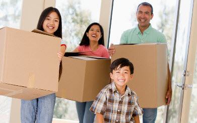 Happy family moves into their new house with boxes